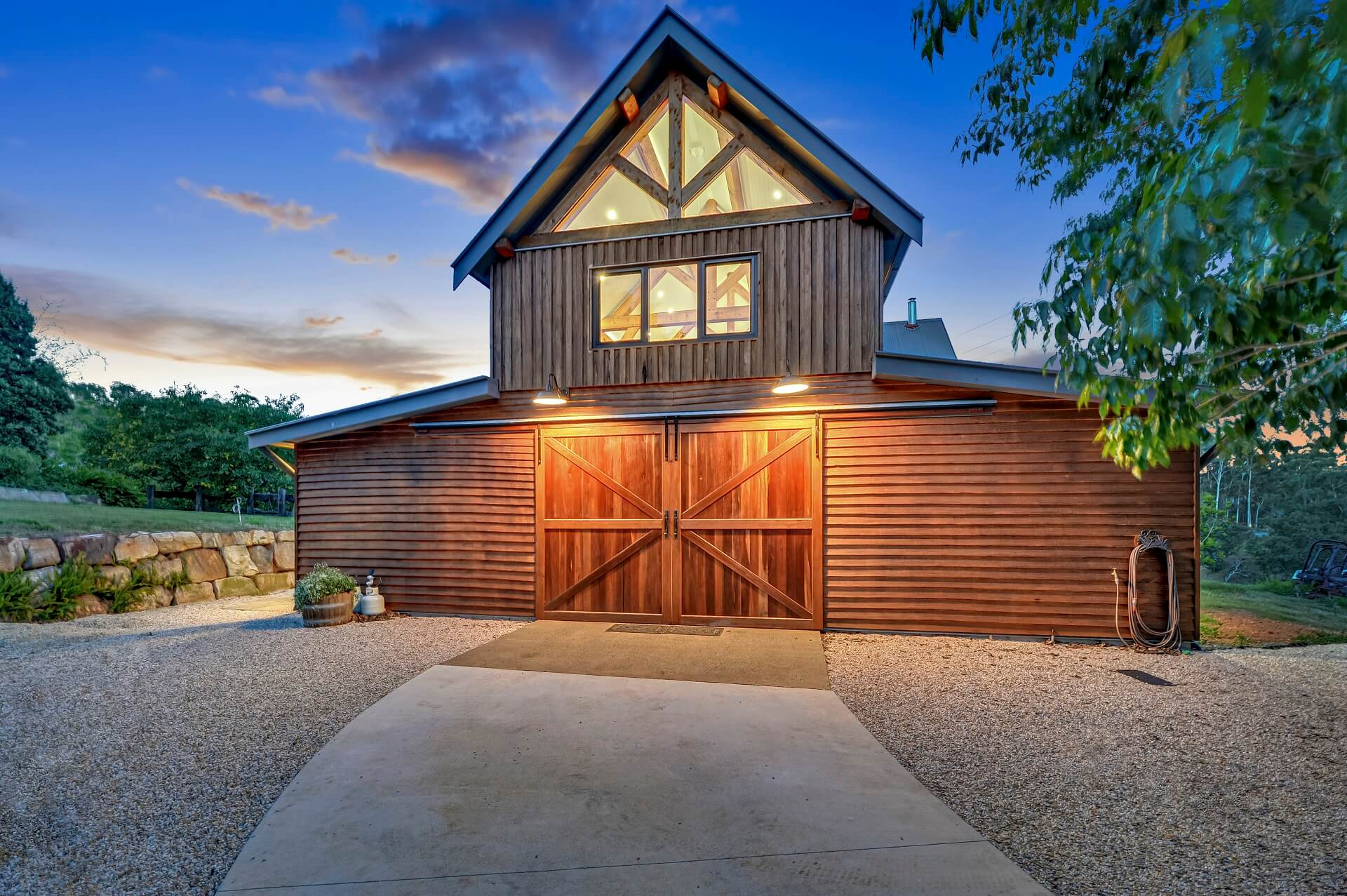 Luxury timber barn exterior feauturing large barn doors, glazed gables and timber cladding