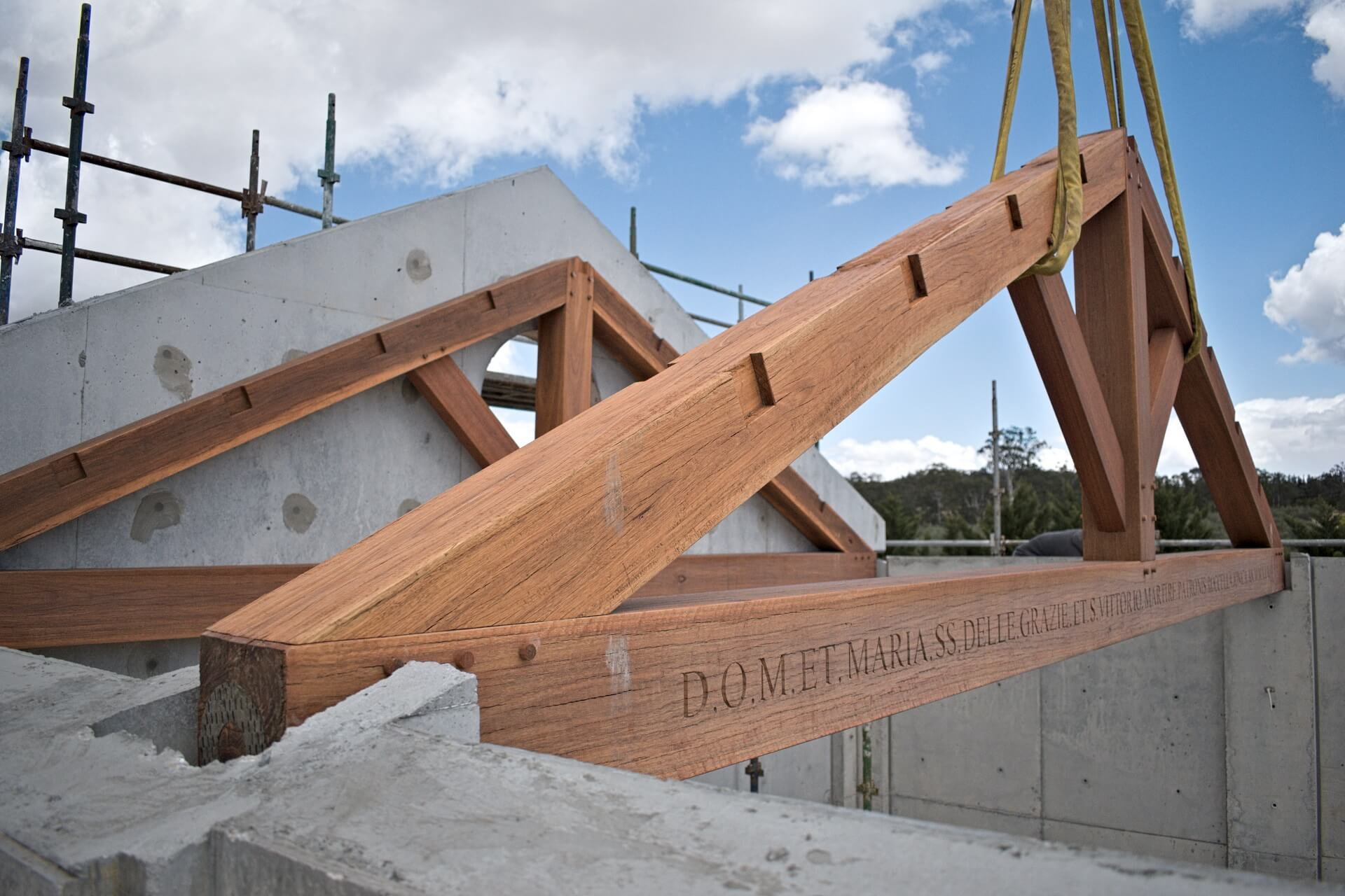 Traditional spotted gum trussed are craned into position on top the pre-formed concrete walls of the chapel. Visible is a hand carved inscription in the beam in Italian