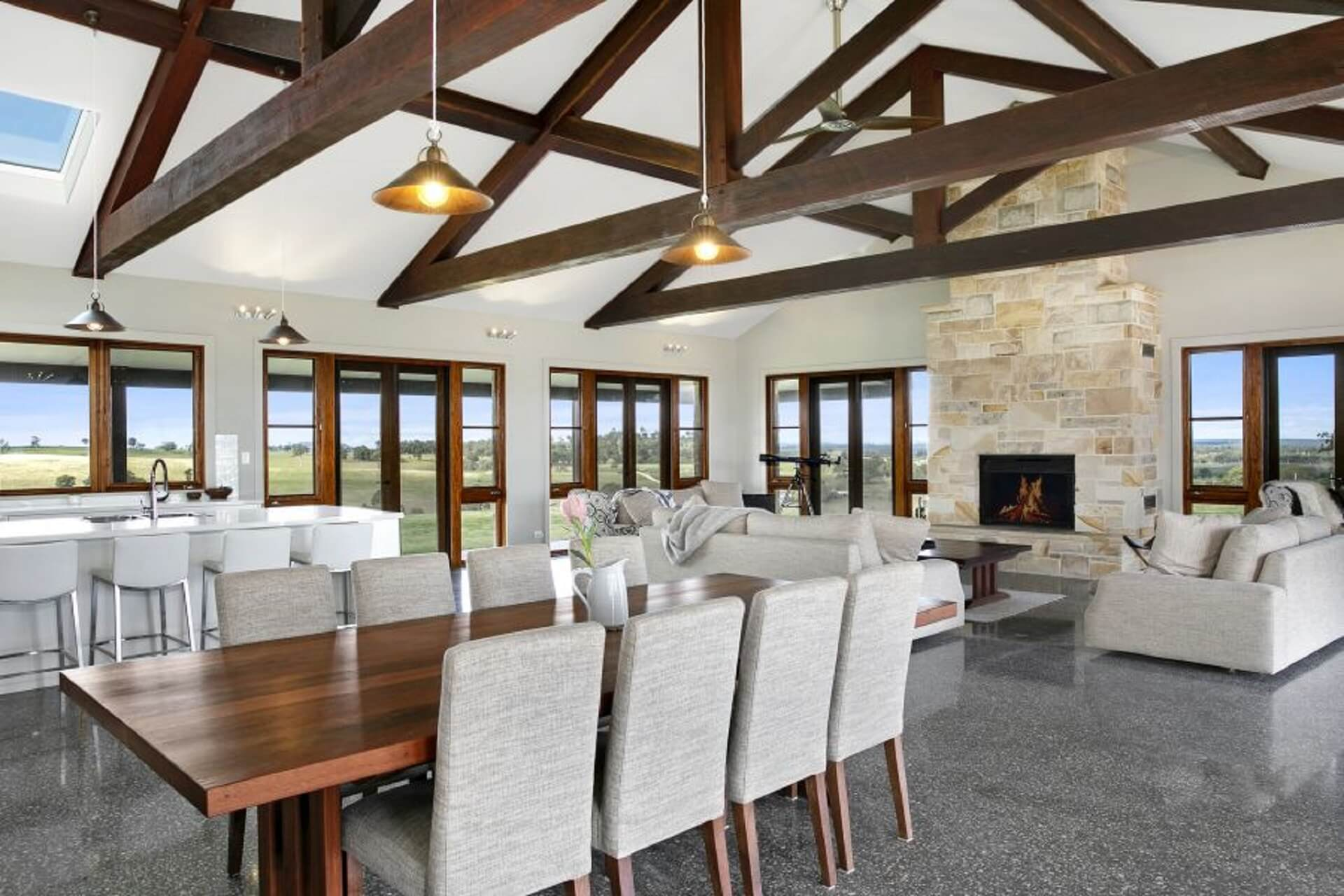 Interior of a luxury open plan living and kitchen. Featuring exposed Ironbark trusses, large quantities of timber framed windows and a sandstone fireplace
