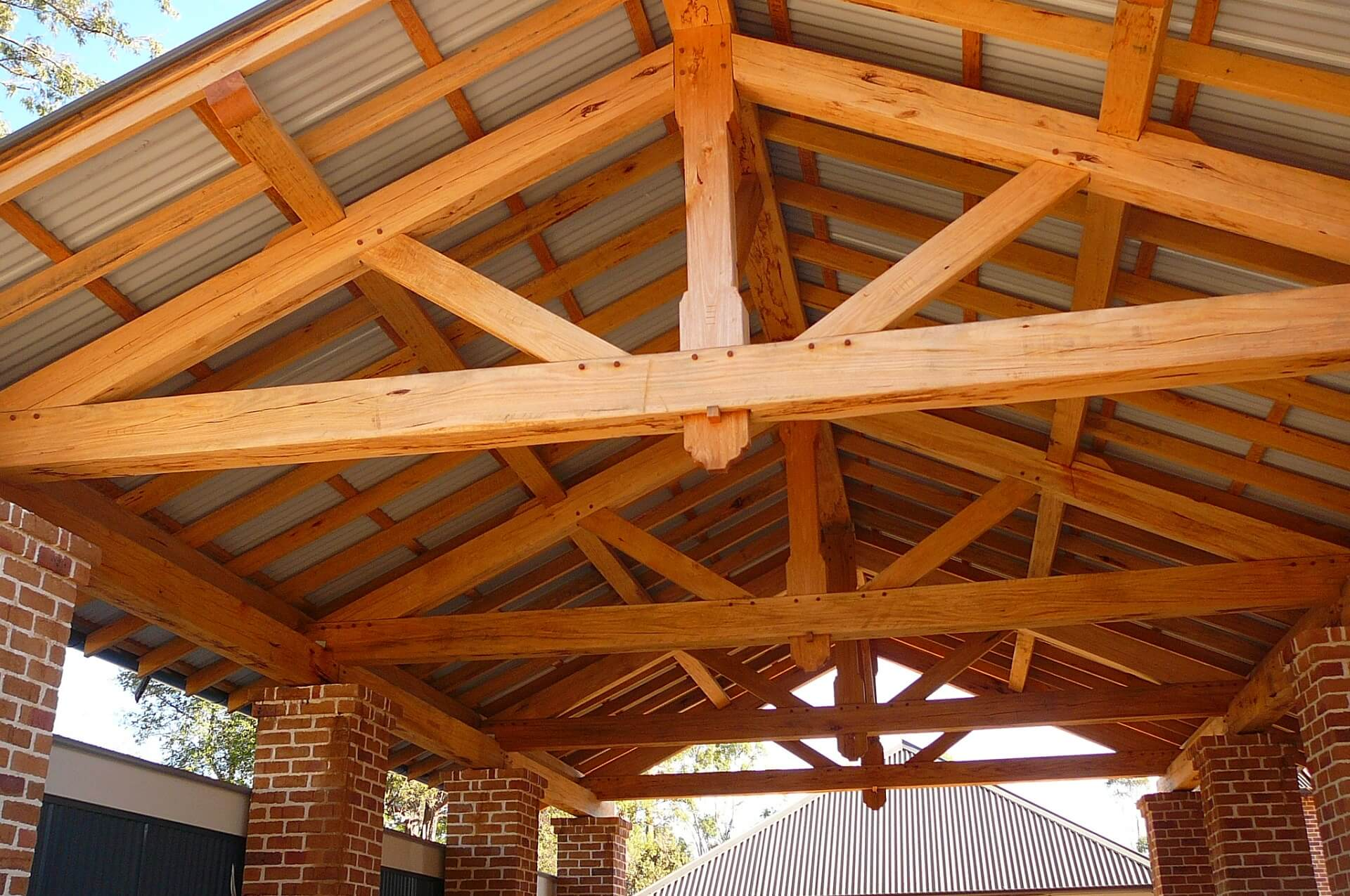 Photo of the completed outdoor pavillion. Featuring traditonally built timber trusses, brick pillars and a corrugated roof