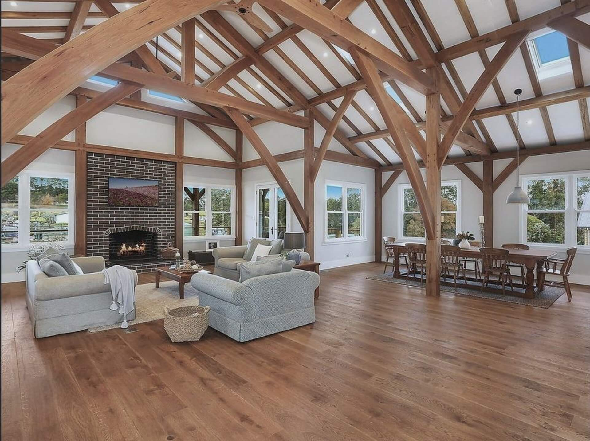 Expansive open plan kitchen, living and dinning. Featuring an exposed traditional timber frame with custom curved braces and federation style brick fireplace