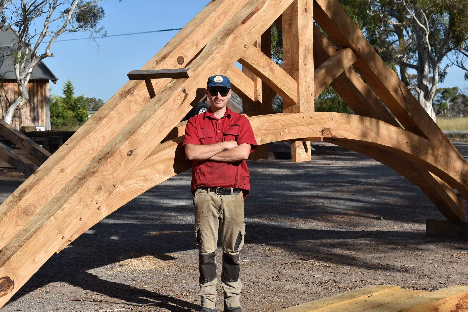 Lead craftsman Andrew Balabka stands proudly by the completed oak trusses