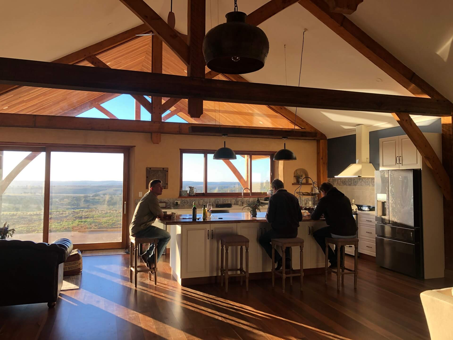 Farm house kitchen with exposed timber beams and trusses, glazed gables and exapnsive views over the countryside